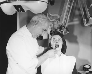 Dentist pulling womans tooth